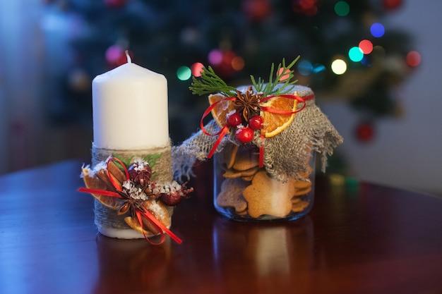 瓶の中のクリスマスキャンドルとñookies。クリスマスのヒイラギ。お祭りの装飾