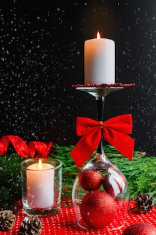 Christmas candle on an inverted glass, spruce pine branches and christmas decorations desi