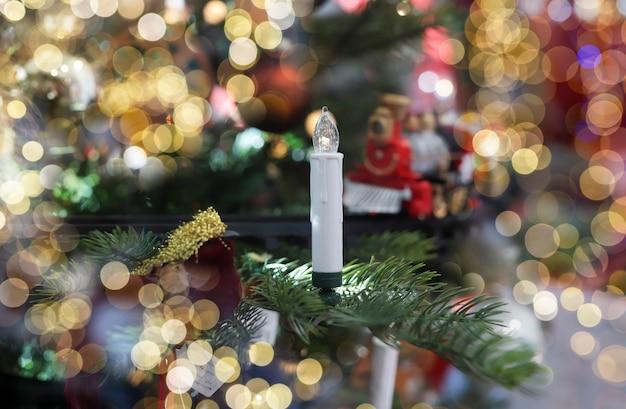 クリスマスの花輪の魔法のぼやけたライトとモミの木のクリスマスキャンドル