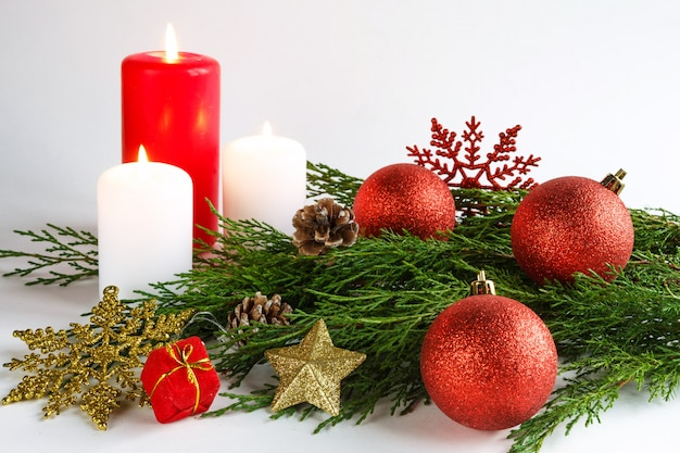 Christmas candle, spruce pine branches and christmas decorations design in a new year's st