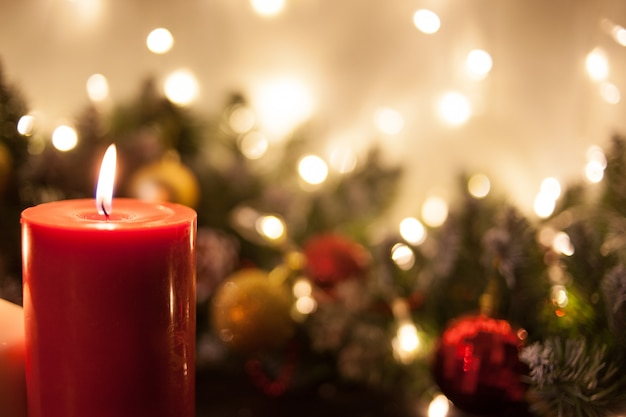 Christmas candles on of branches of a christmas tree and glowing garlands