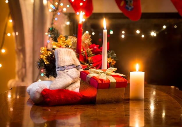 Christmas candles, gift box and woolen sock placed on table against fireplace