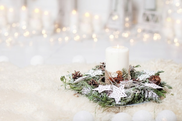 Christmas candles and snowy fir branches over white  background with lights.  new year's decoration with a fir tree in white tones.