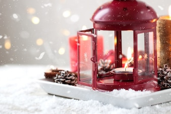 Christmas candles with fir cones, lantern, christmas decoration and snow, winter or holiday concept