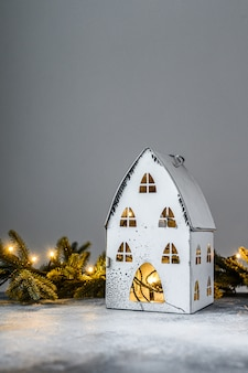 Christmas, candlestick house with lights, fir branches and christmas toys. happy new year.