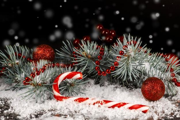 雪の黒い背景にモミの枝とクリスマスキャンディケインと赤いクリスマスボール。