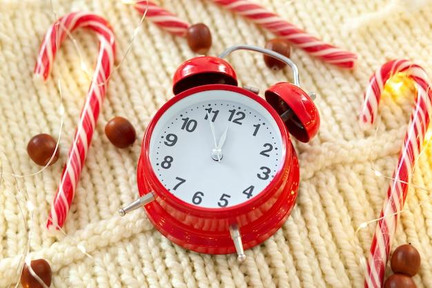 Рождественский леденец, гирлянда и красный будильник