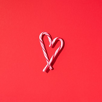 Christmas candy cane heart on red background with copy space. top view. love, valentines day concept. new year and christmas card