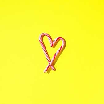 Christmas candy cane heart on yellow background with copy space. top view. love, valentines day concept. new year and christmas card