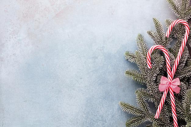 クリスマスのキャンディケインは、青い背景に均等に並んで横たわっていた。フラットレイと上面図