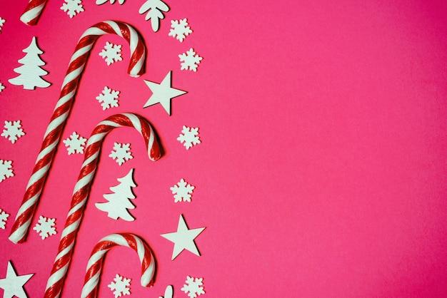 Рождественские леденцы лежали ровно в ряд на розовом фоне с декоративной снежинкой и звездой. плоская планировка и вид сверху.