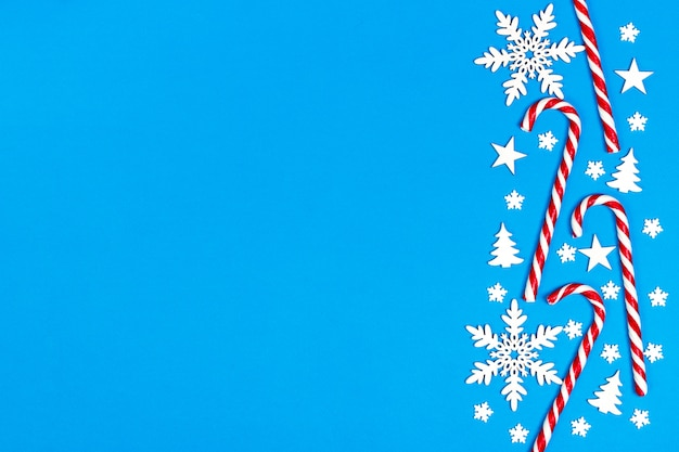 Christmas candy cane lied evenly in row on blue background with decorative snowflake and star. flat lay and top view