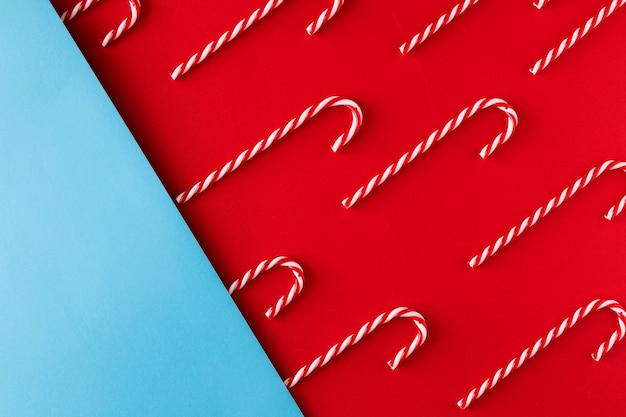 Christmas candy cane on red and blue paper background