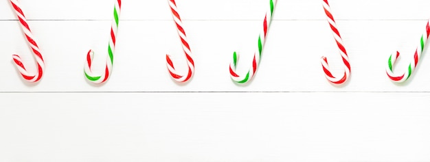 Christmas candy cane sweets on white wood banner backgground