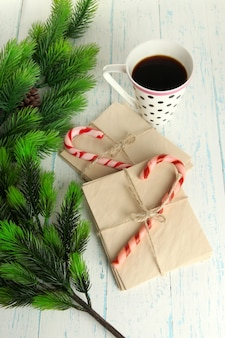 Christmas candy canes, cup with hot drink and letters for santa, on wooden background