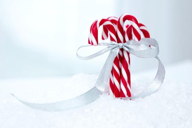 弓で銀のお祝いリボンで結ばれた雪の中でクリスマスキャンディー