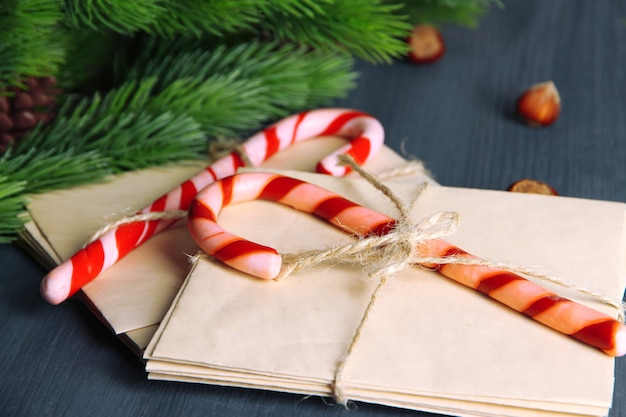 Christmas candy canes and letters for santa, on color wooden surface