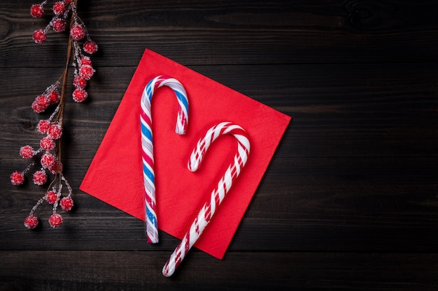 Christmas candy canes on red napkin with frozen red berries on dark wooden table.