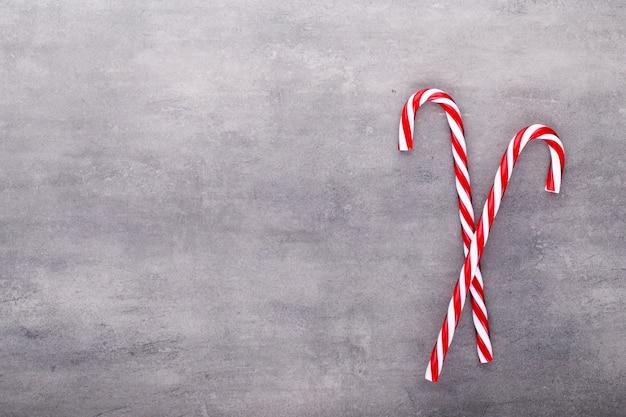 Рождественские леденцы, палка и декор на цветном фоне. сладкая рождественская открытка - леденцы с лентой - изображение.