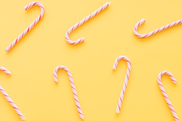 Christmas candy canes on yellow background