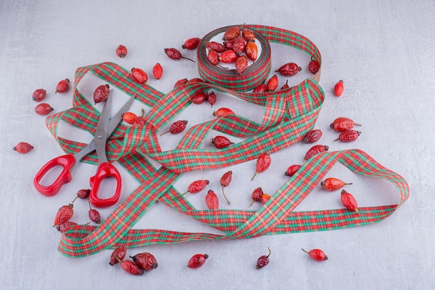 Christmas candy colored ribbons and dog rose fruits on white background.
