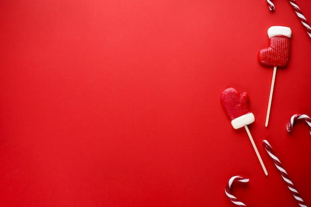 Рождественские конфеты на красном. новогодняя композиция. плоская планировка, copyspace.