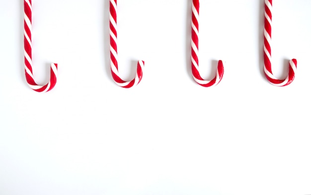 Christmas cane candies lined up on a white background from above.