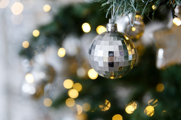 Christmas card and background. christmas toy ball in a cage on a branch, on a background of yellow lights bokeh garlands