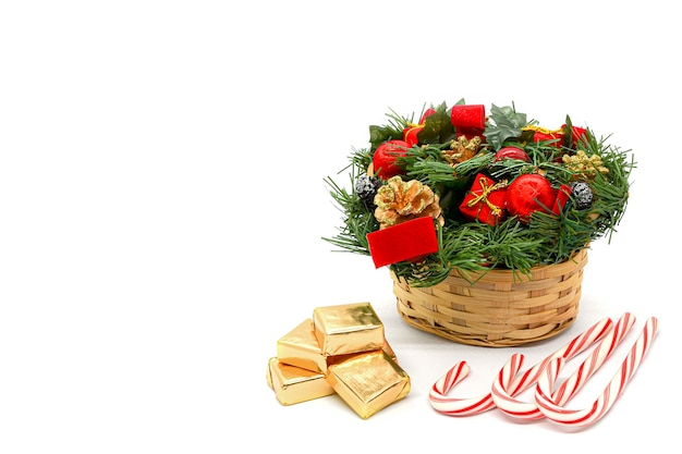 Рождественская открытка: корзина с еловыми ветками, сосновыми шишками и украшениями, леденцы и квадратные конфеты в золотой обертке на белом фоне. место для текста слева.