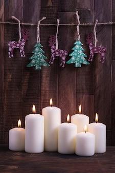 ろうそくや木の背景に木の装飾を燃やすクリスマスカード