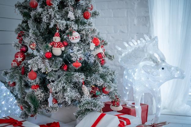 クリスマスカード。おもちゃで飾られたクリスマスツリー、クリスマスツリーの周りに赤いリボンで結ばれた多くの贈り物。氷のおもちゃの鹿。新年のクリスマスのインテリア