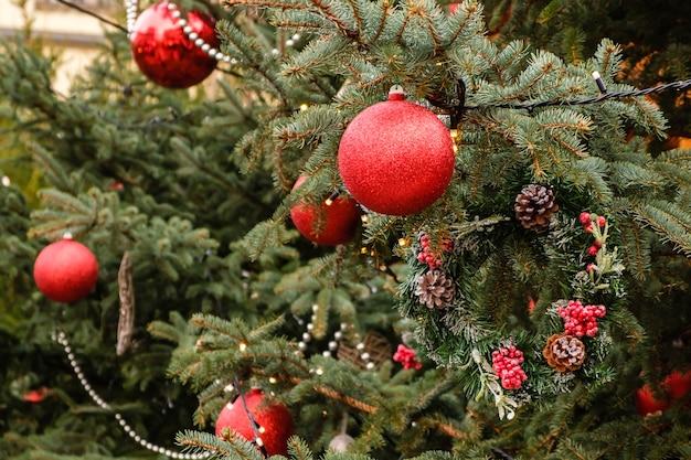Рождественская открытка. крупный план красных новогодних шаров и гирлянды на ветвях естественной рождественской елки на открытом воздухе в солнечный летний день. ни людей, ни снега.