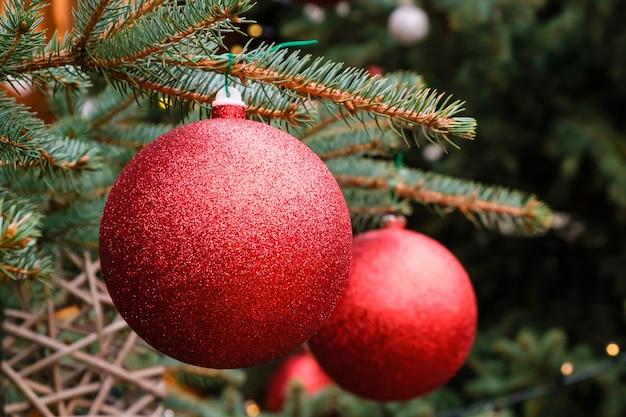 クリスマスカード。屋外の自然なクリスマスツリーの枝に2つの赤い新年のボールのクローズアップ
