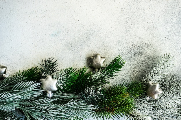 クリスマスカードのコンセプト-コピースペースと石の背景に雪とつまらない装飾と常緑の木の枝で作られたフレーム
