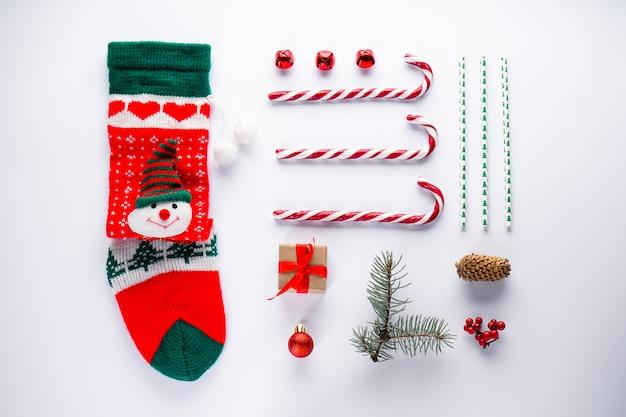 Концепция рождественской открытки с игрушками носка, конфет и новогодних украшений на белом. Premium Фотографии