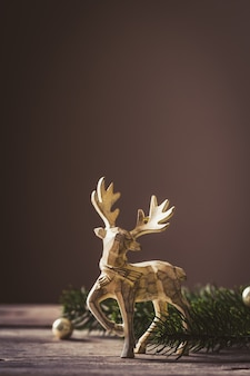 Christmas card conception. christmas toy deer decoration with christmas tree branch and snow.