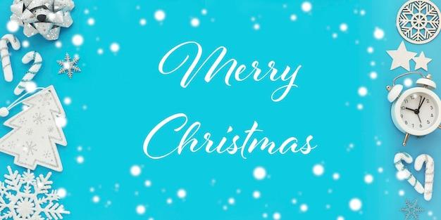 クリスマスカードの装飾的な要素と青い背景の碑文メリークリスマス。