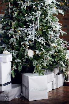 クリスマスカード。真っ白なパッケージの箱に入ったギフトは、茶色の木の床のクリスマスツリーの下にあります。