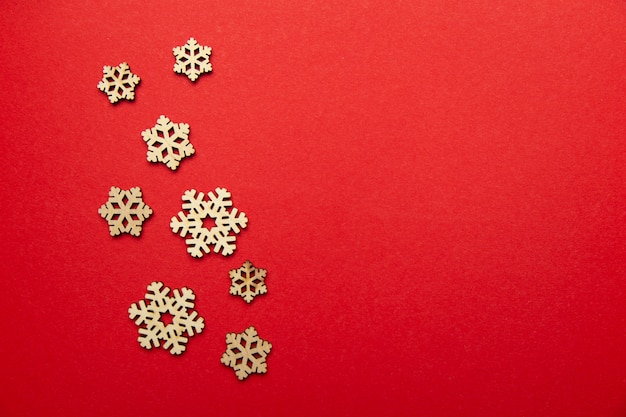 Christmas card made of wooden snowflakes against red . flat lay. view from above.