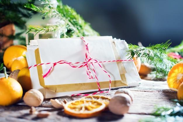 クリスマスカードメリークリスマスと新年あけましておめでとうございますのテーマ。手紙、トウヒ、ランタン、みかん、木の背景にナッツ。