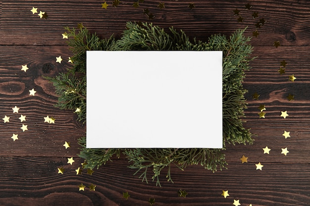 Christmas card mockup template with fir twigs and golden stars on a vintage wooden.