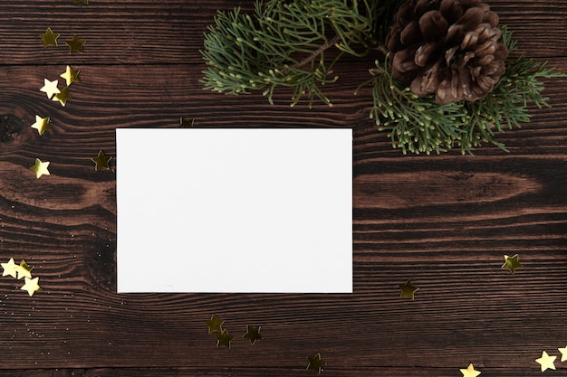 Christmas card mockup template with fir twigs and golden stars on a vintage wooden