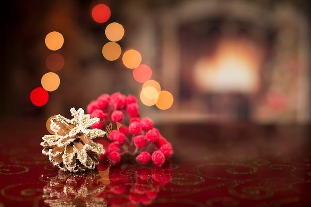 Рождественская открытка. новогодний фон с шишкой боке и заснеженной рябиной