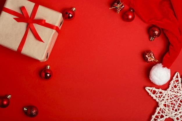 クリスマスカード。赤い背景に赤いボール、クラフトギフトボックス、キャップサンタ、スター。フラットレイ