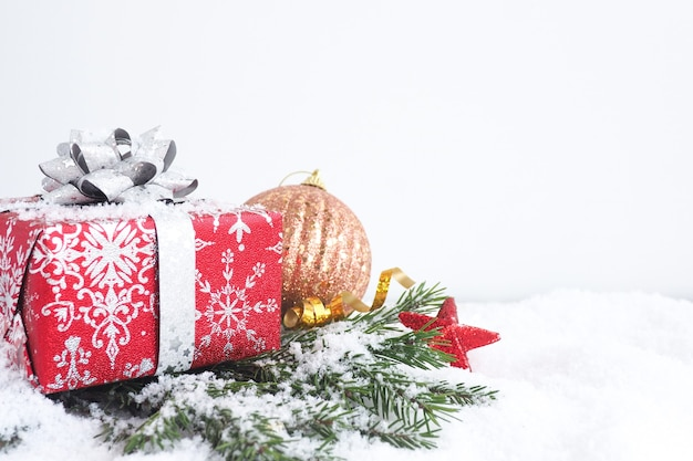 Рождественская открытка. красная подарочная коробка с серебряным бантом на еловых ветках со снегом, звездами и елочным шаром. копировать пространство.