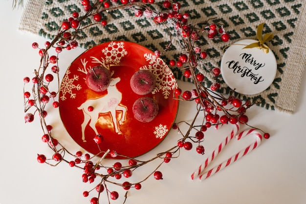 Christmas card. red plate with a deer, candied apples, cane candies and red berries on branches on the table, top view
