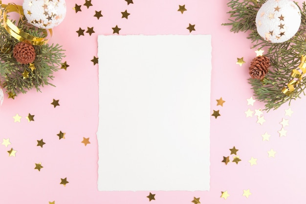 Christmas card template with fir twigs and golden stars and festive decoration on a pink pastel background.