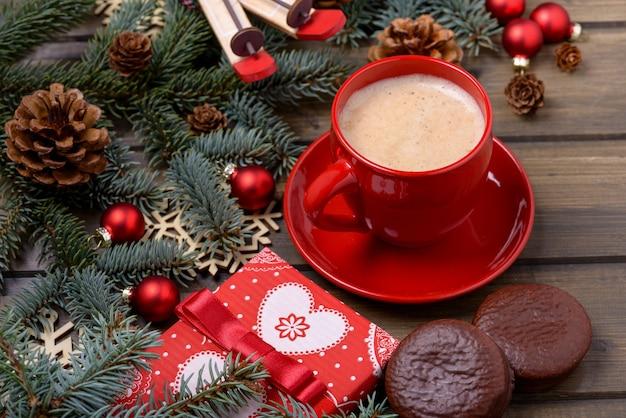 木製の背景にコーヒーとクッキーとクリスマスカード