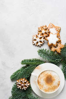 Christmas card with cup of coffe, pine, fir and gingerbread on white background, copy space, top view, vertical