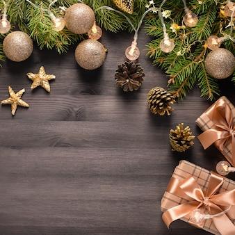 モミの木の枝、金色の装飾、お菓子、松ぼっくりのクリスマスカード。お祝いのクリスマスの背景